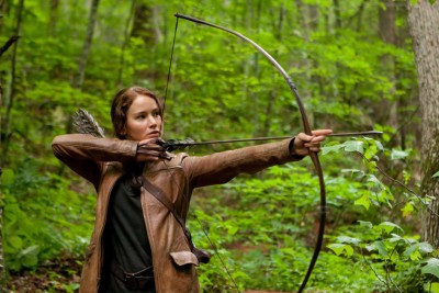 "Katniss Everdeen (Jennifer Lawrence) aims her bow and arrow in ""The Hunger Games."""