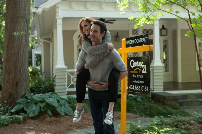 Alex (Rodrigo Santoro) carries preggo Holly (Jennifer Lopez) around the lawn of a Century 21 home.