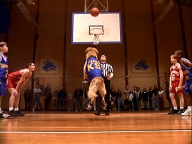 At the free throw line, Air Bud gets an assist from a referee's pass. Still from Air Bud's original DVD - click to view screencap in full 720 x 480.