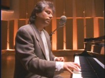 A mulleted Menken performs one of his many famous Disney songs in simpler times.