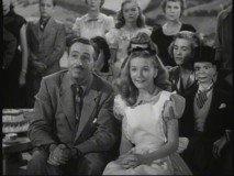 "Walt Disney and Kathryn Beaumont marvel at the Magic Mirror's ability to become a television in the 1950 Christmas special ""One Hour in Wonderland."""