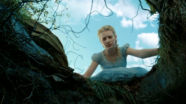 "Nineteen-year-old Alice Kingsleigh (Mia Wasikowska), the 2010 take on Lewis Carroll's protagonist, peers down the famed rabbit hole near the beginning of Tim Burton's ""Alice in Wonderland."""