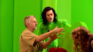 "As eyepatched Red Queen army head Stayne, Crispin Glover has something explained to him by a crew member on the bright green screen set of ""Effecting Wonderland."""
