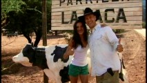 Odette Yustman and director Marcos Efron pose for a pic by the restaurant cow statue in the video diary.