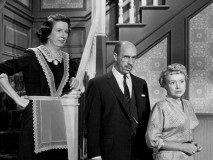 Kate, Archie, and Lila -- the three adults of the McCleod household -- look on from the staircase in the final episode.