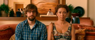 Burt (John Krasinski) and Verona (Maya Rudolph) stay still while a mother and son use Verona's pregnant stomach as a teaching exercise.