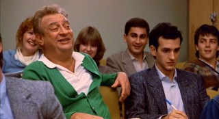 On his first day of school, Thornton Melon (Rodney Dangerfield) has his Grand Lakes University classmates laughing, while his son (Keith Gordon) seems less amused.