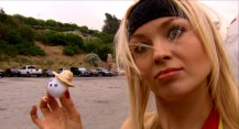 "Model/Playmate Irina Voronina has a small part in the film, but does more acting in the featurette ""Under the Balls"", in which she poses as a quirky ""ball wrangler."" Here, she shows off a little ping-pong ball with a face and straw hat."