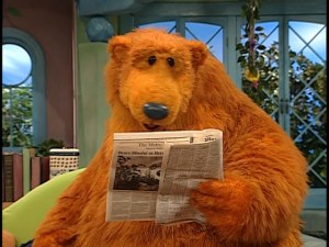 Bear looks for words in the newspaper.