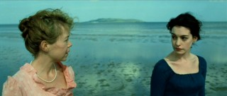 Cassandra (Anna Maxwell Martin) takes a beachside walk with Jane (Anne Hathaway) to muse over recent concerns.