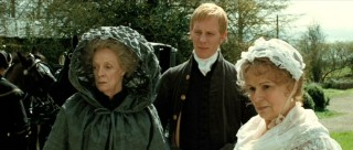 Lady Gresham (Maggie Smith), Mr. Wisley (Laurence Fox), and Mrs. Austen (Julie Walters) observe as Jane (Anne Hathway) jots down her thoughts after being visited by the muse.