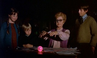 With the children watching, Eglantine tries to cast a spell and succeeds at making the bedknob light up in pink.