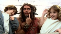 "Dressed up like a satyr for the Ancient Rome sequence, Russell Brand goofs around with child actors Jonathan Morgan Heit and Laura Ann Kesling in ""To All the Little People."""