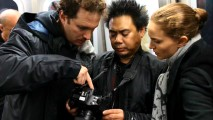 Mustachioed director Darren Aronofsky, cinematographer Matty Libatique, and Natalie Portman examine a digital camera as part of their New York City subway shoot.