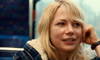 Sharing a bus, Cindy (Michelle Williams) smiles as Dean simultaneously compliments and insults her.