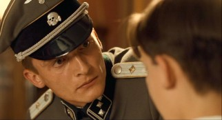 Young Nazi Lieutenant Kurt Kotler (Rupert Friend) maintains a temperamental presence around the family's new house.