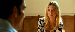 Laura (Emma Booth) politely listens while Joe shares his concerns with what he thinks is his son's teacher.