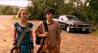Leslie Burke (AnnaSophia Robb) and Jess Aarons (Josh Hutcherson) walk from their bus stop into the forest that will become their frequent playground.