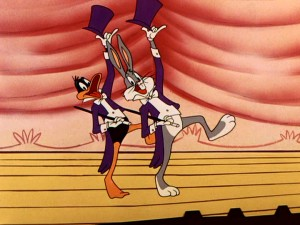 "Daffy Duck and Bugs Bunny dance together before throwing it down in ""Show Biz Bugs."" Thanks to consistent wardrobe, this final cartoon of the movie blends with the Oswald Award bits around it."