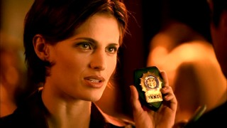 Homicide detective Kate Beckett (Stana Katic) is all business as she flashes her NYPD badge.