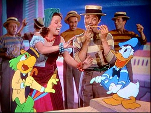 "Aurora Miranda, Joe Carioca, and Donald Duck dance in ""The Three Caballeros"", while the mustachioed man makes music with a pencil and his teeth."
