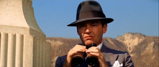 J.J. Jake Gittes (Jack Nicholson) illustrates his career as a private investigator with an interested look and a pair of binoculars.