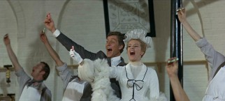 Caractacus (Dick Van Dyke) and Truly (Sally Ann Howes) are excitedly joined by Lord Scrumptious' factory workers in holding up Toot Sweets, the candy you can use as a flute.