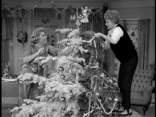 "Vivian Vance (Vivian Bagley) and Lucy Montgomery (Lucille Ball) hurriedly try to make one happy Christmas tree from the two they've ruined for each other in ""The Lucy Show"" episode ""Together for Christmas."""