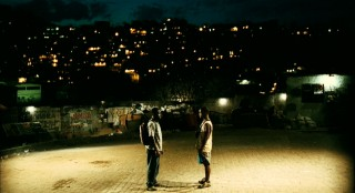 With Rio de Janeiro's scattered lights behind them and gang warfare around them, Ace and Wallace call it a night.