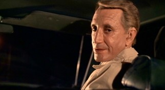 Unrealistically lit seasoned hitman Mr. Cohen (Roy Scheider) exhibits a tiny modicum of warmth as he answers fearful Travis' questions.