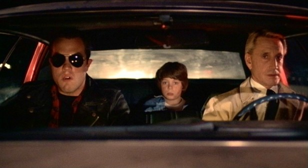 Tate (Adam Baldwin), Travis (Harley Cross), and Cohen (Roy Scheider) act cool as they slowly move through a highway police check point.