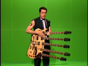 "Against green screen, Colbert pulls out the five-necked guitar of Cheap Trick's Rick Nielsen for ""Rock and Awe: Countdown to Guitarmageddon."""
