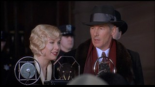 Richard Gere is perplexed that even the microphone can't strengthen his singing voice.