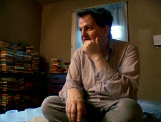 Troubled older brother Charles Crumb sits among his old books in the house he still shares with his mother and her cats.