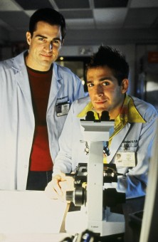 Former jock Nick Stokes (George Eads) and his lab-coated friend (Eric Szmanda) take a break from their microscopic work to smile for the camera.