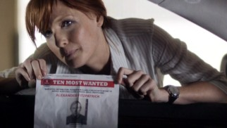 Detective Inspector Anna Travis (Kelly Reilly) holds up a print-out on one of the FBI's Ten Most Wanted criminals.