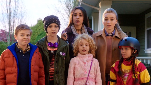 "Circumstances require Lola (Sofia Carson) and Jenny (Sabrina Carpenter) to take the Andersons' SUV and the five kids they're watching into the city in ""Adventures in Babysitting."""