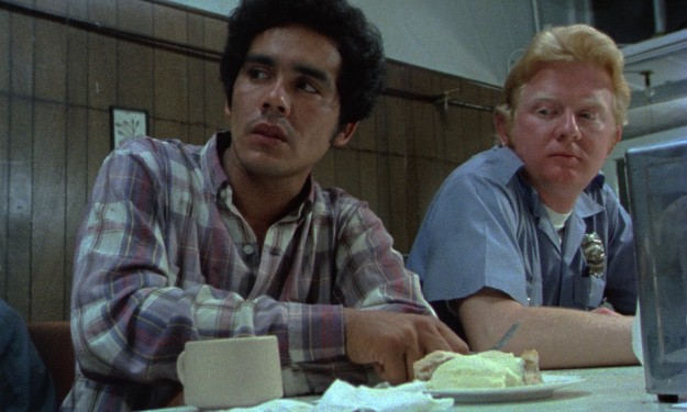 "Illegal alien Roberto Ramírez (Domingo Ambriz) is a bit uncomfortable about trying his favorite diner's apple pie and ice cream at a counter next to a cop (Officer Mark Herder) in ""¡Alambrista¡"""