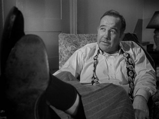 Now a big shot, Governor Willie Stark (Broderick Crawford) sits back and puts his feet up as he tells officials to write him an undated resignation letter.