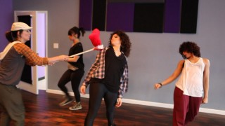 "A red pillow on a stick fills in for a Chipette in the dance rehearsal of ""Everybody Munk Now!"""