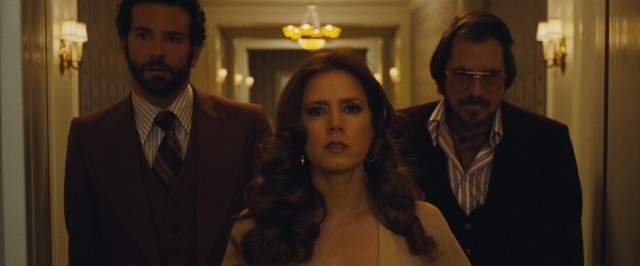 "The title ""American Hustle"" is laid over this shot of Richie (Bradley Cooper), Sydney (Amy Adams), and Irving (Christian Bale) walking into an important meeting."
