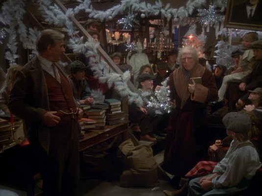 The Ghost of Christmas Present (Gerard Parkes) brings Benedict Slade (Henry Winkler) to an orphanage decorated with white garland.