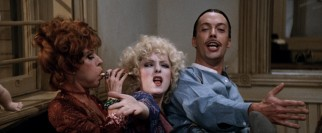 Miss Hannigan (Carol Burnett), Lily (Bernadette Peters), and Rooster (Tim Curry) gleefully celebrate an evil plot to make them rich.