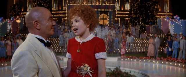 Daddy Warbucks (Albert Finney) and little orphan Annie (Aileen Quinn) get a happy ending together full of lights and Fourth of July fireworks.
