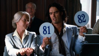 An intoxicated Arthur (Russell Brand) amuses himself (but not Helen Mirren) with an auction bidding war with himself.