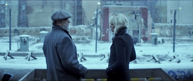 Lorraine Broughton (Charlize Theron) meets with American CIA agent Emmett Kurzfeld (a white bearded John Goodman) by the Berlin Wall.