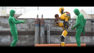 """The Making of 'Automata'"" shows behind-the-scenes footage of men in green body suits operating the robots."