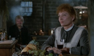 Babette Hersant (Stéphane Audran) enjoys a glass of wine while diners in the next room enjoy the ornate multi-course feast she has prepared for them.