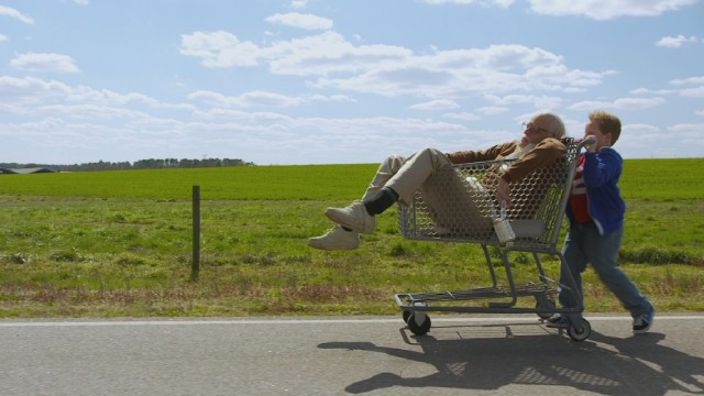 "Eight-year-old Billy (Jackson Nicoll) pushes his drunken grandfather Irving Zisman (Johnny Knoxville) around in a shopping cart in ""Jackass Presents: Bad Grandpa."""