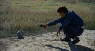 Kit shoots a football in the Badlands.